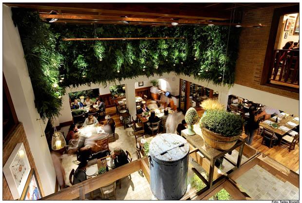 Salão com móveis rústicos e jardins verticais projeto do arquiteto