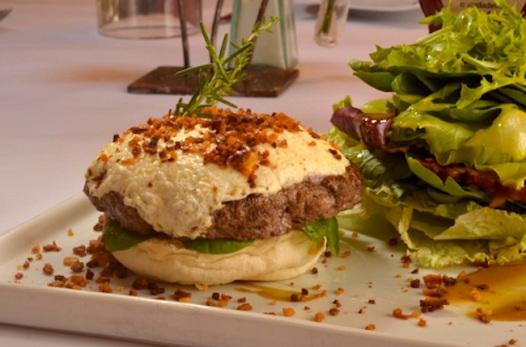 Hambúrguer de cordeiro com queijo de cabra brûlé e farofa de bacon, do Ruella