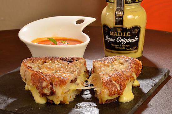 Grilled Olive Cheese (R$ 15), do Santo Pão: mix de queijos derretidos no pão artesanal de azeitonas e alecrim tostado na chapa, acompanha dipping de tomate e manjericão.